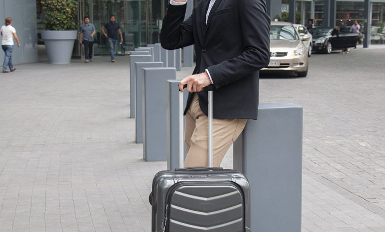 A man with a suitcase talking on his phone