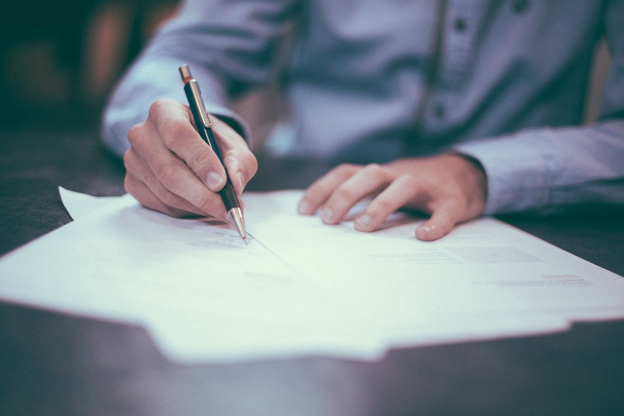 a man holding a pen writing on a paper